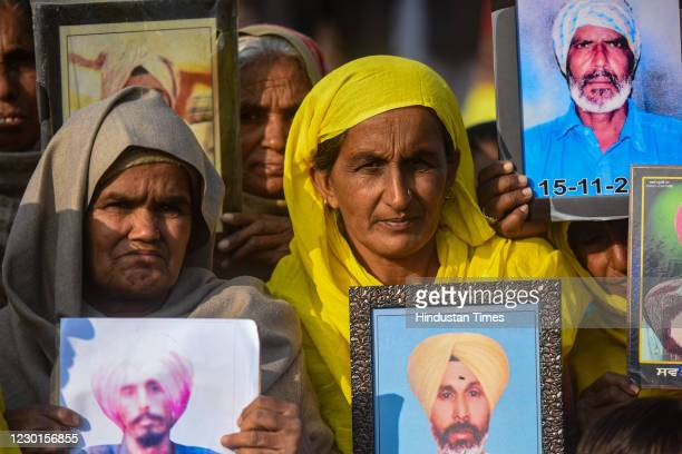 Relatives of farmers who are believed to have died by suicide over debt issues, seen holding photographs of the deceased during the ongoing protest...