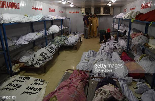 Relatives of heatwave victims stand as dead bodies are seen in the the cold storage of the EDHI morgue in Karachi on June 21 2015 A heatwave has...