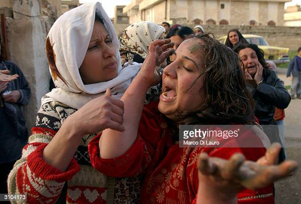 Relatives of Iraqi policeman Ali Akram who was killed in a suicide bomb attack outside an Iraqi police station weep February 23 2004 in Kirkuk Iraq A...