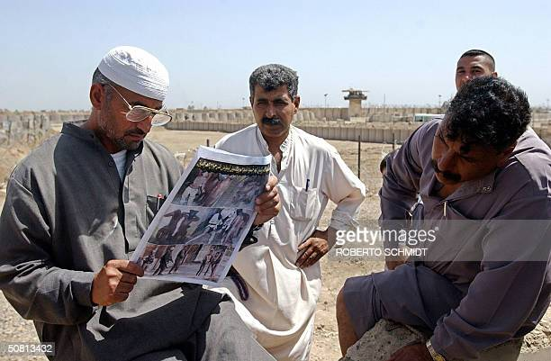 Relatives of Iraqi prisoners being held by US authorities at the Abu Ghraib prison look 08 May 2004 at a newspaper featuring photos of US soldiers...