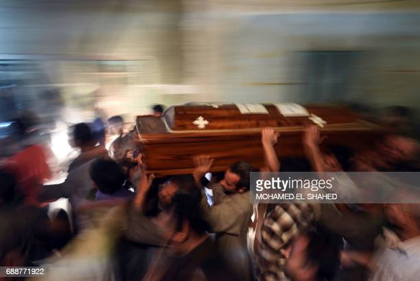 TOPSHOT Relatives of killed Coptic Christians carry a coffin as they gather outside the Abu Garnous Cathedral in the north Minya town of Maghagha on...