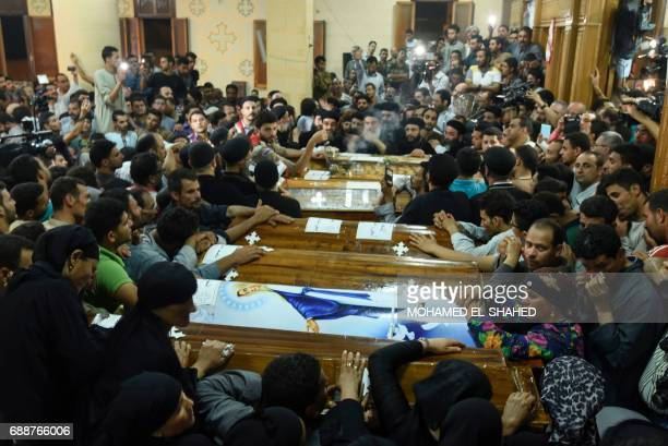 Relatives of killed Coptic Christians grieve by the coffins during the funeral at Abu Garnous Cathedral in the north Minya town of Maghagha, on May...