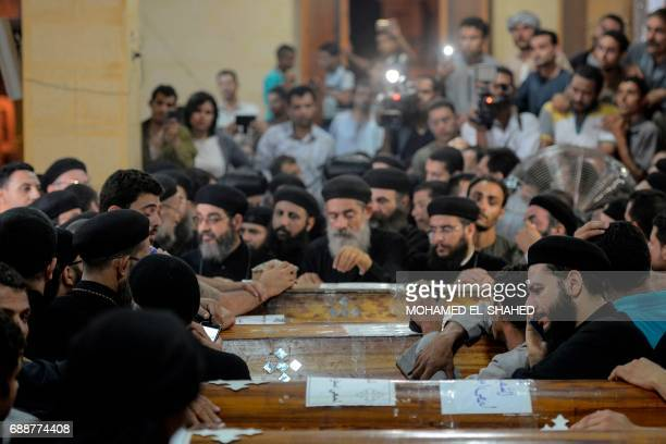 Relatives of killed Coptic Christians grieve by the coffins during the funeral at Abu Garnous Cathedral in the north Minya town of Maghagha on May 26...