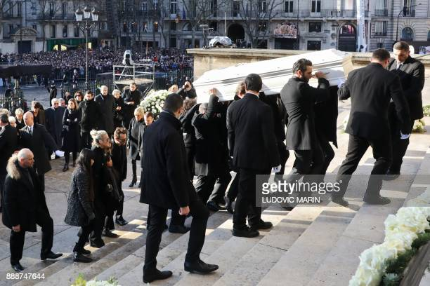 Relatives of late French singer Johnny Hallyday carry his coffin as they enter the La Madeleine Church prior to the funeral ceremony on December 9...