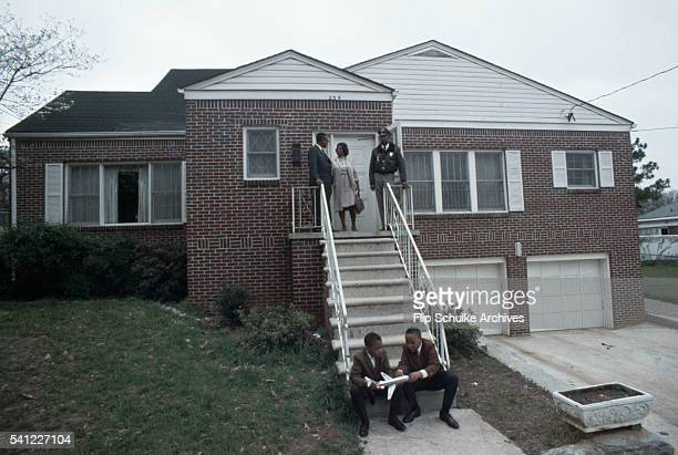 Relatives of Martin Luther King Jr and a security guard stand on the steps of his house during the week of his funeral Two boys sit at the base of...