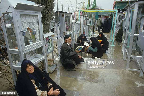 Relatives of martyrs sit at their son's tombs in Behesht-e Zahra cemetery, Tehran, where thousands of those killed in the Iranian Revolution and the...