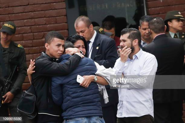 Relatives of Members of the Colombia Police Department embrace near the scene where a car bomb exploded on January 17 2019 in Bogota Colombia A car...