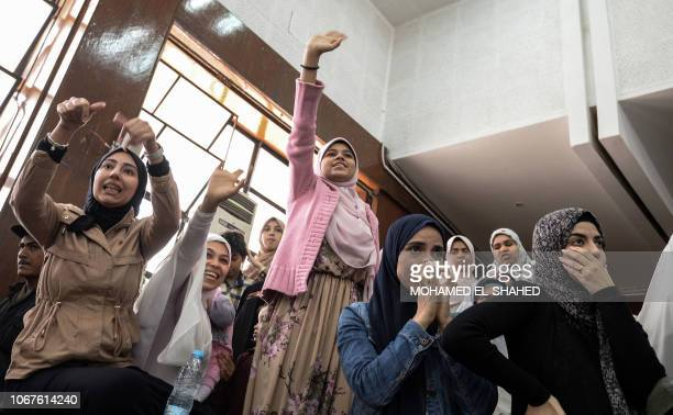 Relatives of members of the Muslim Brotherhood under trial wave and gesture for solidarity during a trial session for them and former Egyptian...