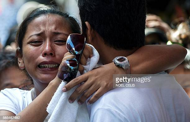 Relatives of Michael Siaron grieve during his burial ceremony at a cemetery in Manila on August 3 2016 Siaron was killed by suspected vigilantes on...