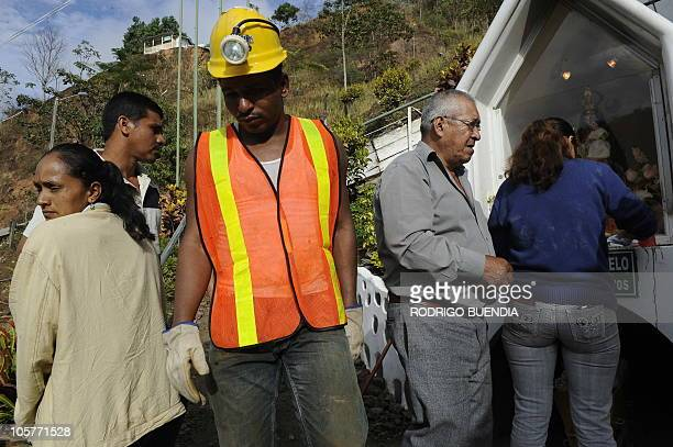 Relatives of miners pray before a statue of Virgen del Consuelo patron saint of the miners at the Casa Negra mine in Portovelo Ecuador on October 20...