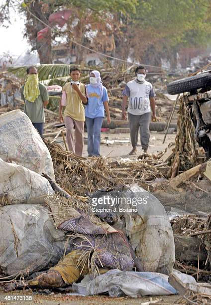 Relatives of missing family members walk towards a victim of the Dec 26th Tsunami in Banda Aceh Indonesia 150 miles from southern Asia's massive...