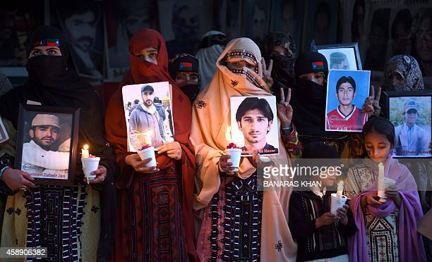 Relatives of missing Pakistanis hold up a portraits of loved ones during a vigil for Baloch Martyrs Day in Quetta on November 13 2014 A campaign...