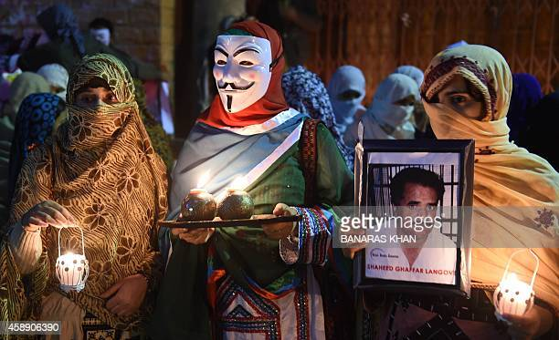 Relatives of missing Pakistanis one wearing a Guy Fawkes mask and another holding a portrait of a loved one participate in a vigil for Baloch Martyrs...