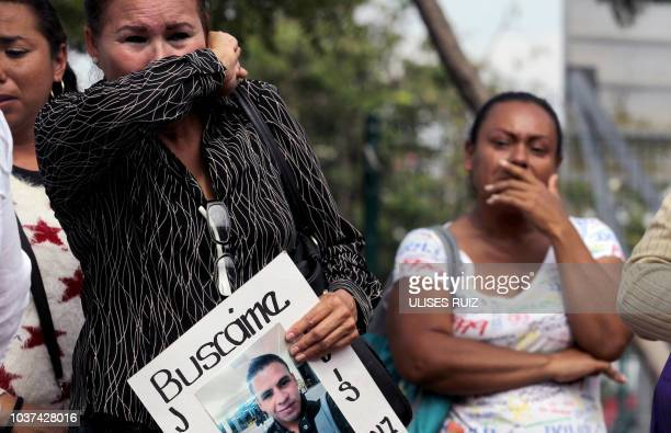 Relatives of missing people cover their faces to avoit the smell as they protest outside the Institute of Forensic Sciences where two trailers remain...
