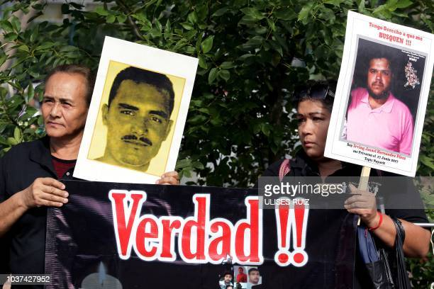Relatives of missing people from Michoacan Sinaloa Nayarit and Mexico states hold portraits of their loved ones as they protest outside the Institute...