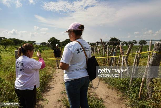 Relatives of missing people wait on September 17 at the entrance the site where a mass grave was found in El Arbolillo Alvarado municipality in the...
