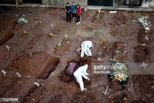 Relatives of Neide Rodrigues who died of the coronavirus disease mourn at the Caju cemetery on May 8 2020 in Rio de Janeiro Brazil According to the...