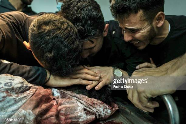 Relatives of Palestinian Izz al-Deen Helles during his bid farewell at Al-Shifa Hospital, after he was killed during an Israeli raid east of Gaza...