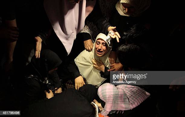 Relatives of Palestinian Marwan Sleem mourn during his funeral in the central Gaza Strip Gaza on July 7 2014 Israeli airstrikes aiming Gaza leave 9...