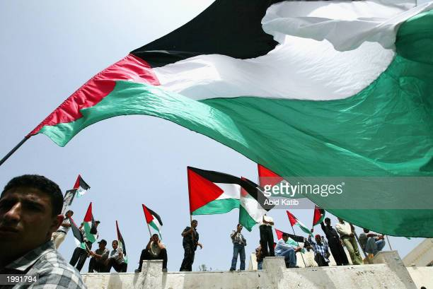 Relatives of Palestinian prisoners being held in Israeli jails wave their national flags as they attend a rally calling for their release May 12 2003...
