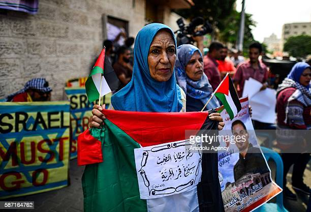 Relatives of Palestinians imprisoned in Israeli jails hold posters during a demonstration demanding the release of Israeliheld Palestinian prisoners...