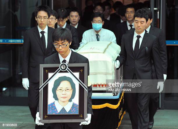 Relatives of Park WangJa who was killing at Mount Kumgang resort in North Korea carry her portrait and coffin during a funeral ceremony at Asan...