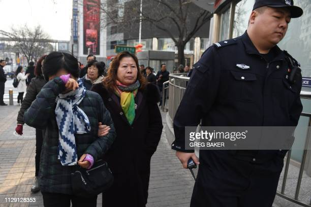 Relatives of passengers of missing Malaysia Airlines flight MH370 walk to the Foreign Ministry in Beijing on March 8, 2019. - Relatives gathered and...