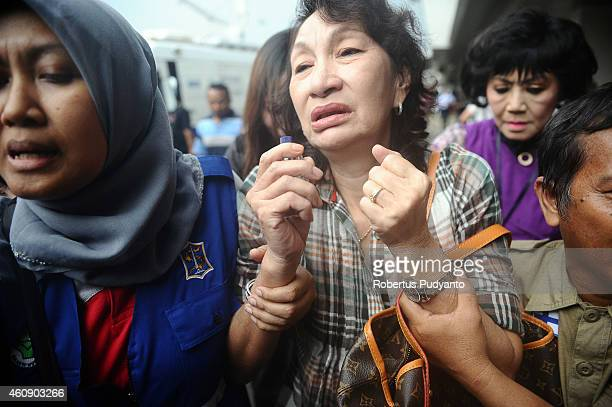 Relatives of passengers on AirAsia flight QZ 8501 react to the breaking news of debris and bodies being found on December 30 2014 in Surabaya...