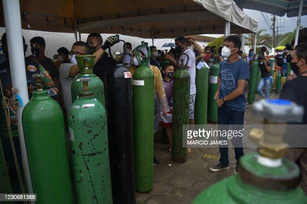 Relatives of patients infected with Covid-19 queue for long hours to refill their oxygen tanks at the Carboxi company in Manaus, Amazonas state,...