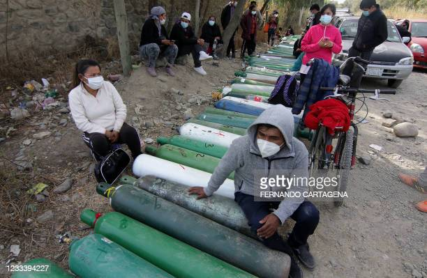 Relatives of patients infected with COVID-19 wait to get oxygen tanks refilled at a refilling centre in Vinto, 26 km west of Cochabamba, Bolivia, on...