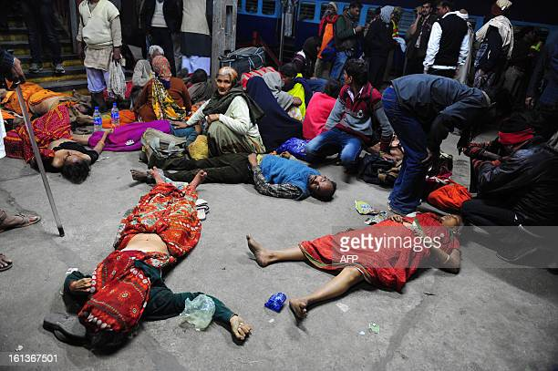 Relatives of people who died in a stampedem sit among the corpses of their relatives at the train station in Allahabad on February 10 2013 At least...