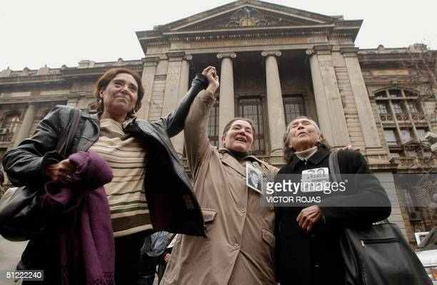Relatives of people who suffered repression during Augusto Pinochet's military regime celebrate in front of the Supreme Court in Santiago 26 August...