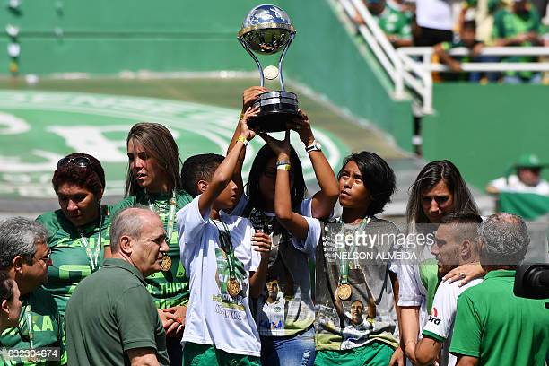 Relatives of players who died in the LaMia airplane crash in Colombia hold the Copa Sudamericana trophy at the Arena Conda stadium in Chapeco Santa...