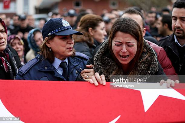 Relatives of police officer Erdem Ozcelik who was killed in bomb attacks outside the Vodafone Stadium in Besiktas on December 10 mourn over his...