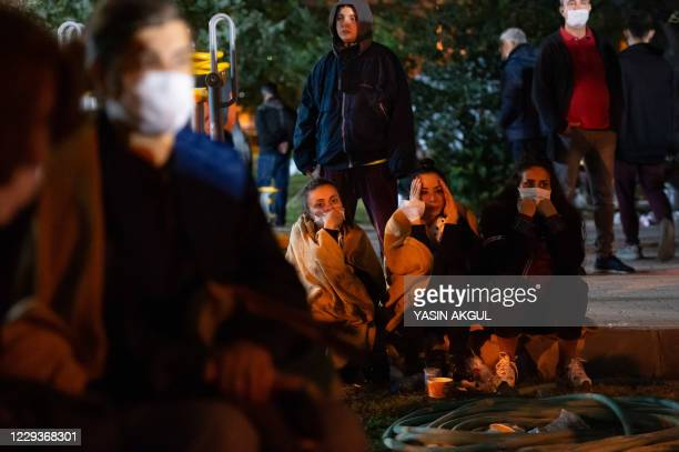 Relatives of potential victims wait as rescuers search for survivors among the rubble of a collapsed building after a powerful earthquake struck...