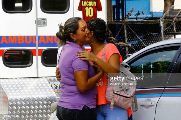 Relatives of prisoners cry in front of a police station in Valencia on March 28 after a fire engulfed police holding cells that resulted in the...