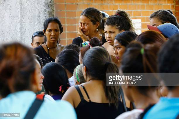 Relatives of prisoners react in front of a police station in Valencia on March 28 after a fire engulfed police holding cells that resulted in the...