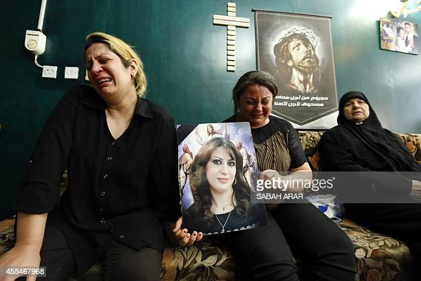Relatives of Raghda Yaqub a 24yearold Iraqi Christian woman killed in a bombing a few days before her wedding hold her portrait as they grieve over...