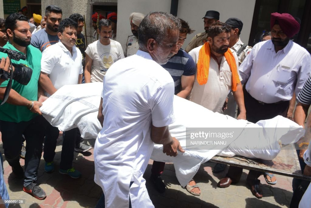 Relatives of slain Congress party councillor Gurdeep Singh Pehalwan carry his body for a postmortem examination at the Civil Hospital in Amritsar on..