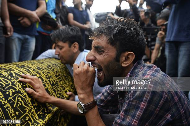 Relatives of slain editorinchief of the Srinagarbased newspaper Rising Kashmir Shujaat Bukhari mourn over the coffin during his funeral procession at...