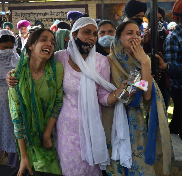 Relatives of slain government school principal Supinder Kour mourn during a funeral procession, on October 8, 2021 in Srinagar, India.