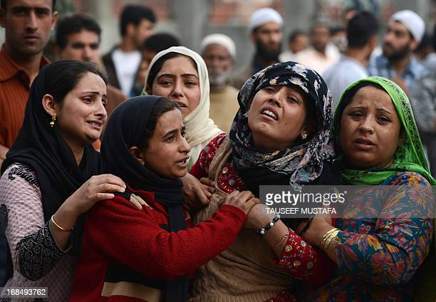 Relatives of slain Indian police officer Farooq Ahmed mourn during a funeral in Srinagar on May 10, 2013. Assistant Sub-Inspector Farooq Ahmad was...