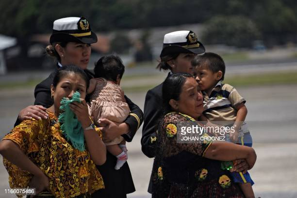 Relatives of soldiers killed in El Estor municipality, Izabal department, react upon the arrival of their coffins at the Air Force Base in Guatemala...
