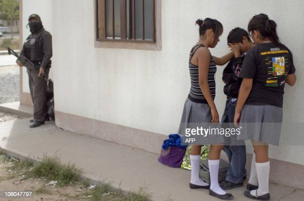 Relatives of some of the 14 partygoers killed when gunmen broke into a home in Ciudad Juarez on October 23 cry during the funeral in this Mexican...