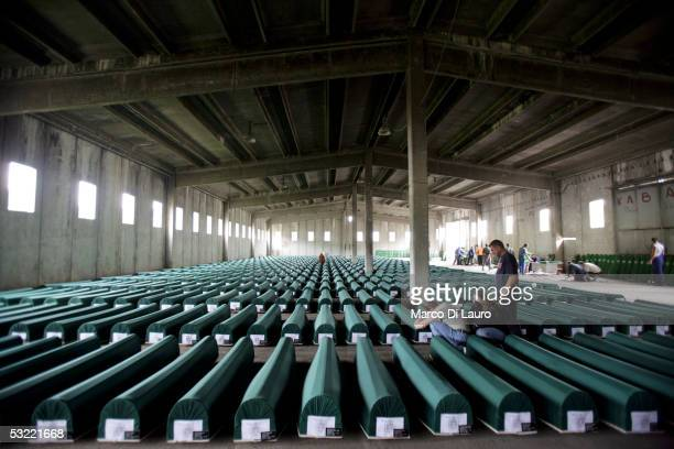 SREBRENICA BOSNIA HERZEGOVINA JULY 10 Relatives of Srebrenica massacre victims mourn in front of one of the 610 coffins containing the remains of...
