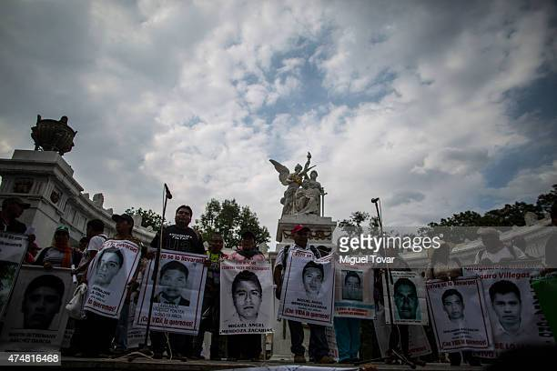 Relatives of the 43 missing students of Ayotzinapa college protest and show pictures during a rally to ask Mexican authorities to continue the search...