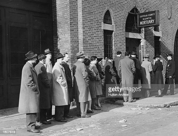 Relatives of the 490 people killed in the Cocoanut Grove nightclub fire wait in line outside a mortuary to identify the bodies of their loved ones...