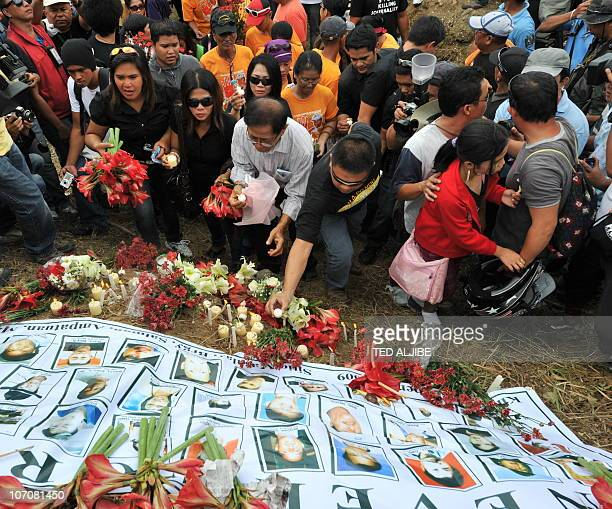 Relatives of the 57 people killed in the massacre on November 23 2009 offer flowers and candles during a memorial service as part of the national day...