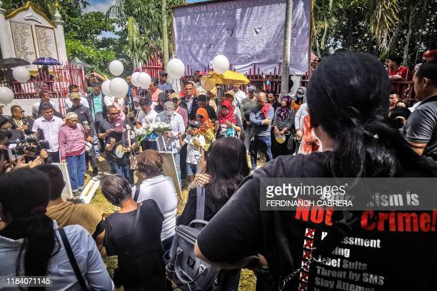 Relatives of the 58 people slain in the country's worst political massacre visit the site of the massacre where markers represented each of the...