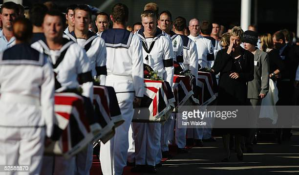 Relatives of the Australian sevicemen and women who were killed in Indonesia walk past their coffins as their bodies are returned to Sydney airport...